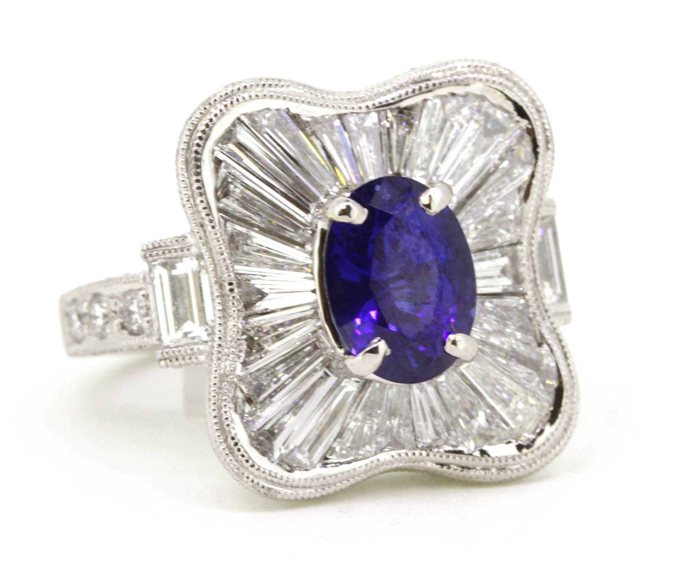 Estate ring in platinum with sapphire center and diamond halo